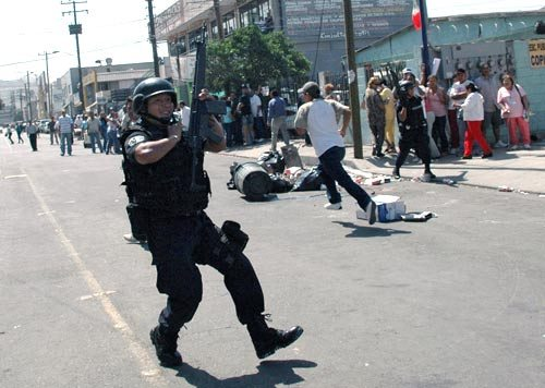 A policeman runs by the La Mesa State Penitentiary in Tijuana, Mexico, where a second riot in three days left at least 17 people dead. September 18, 2008. (Said Betanzos / AFP / Getty Images)
