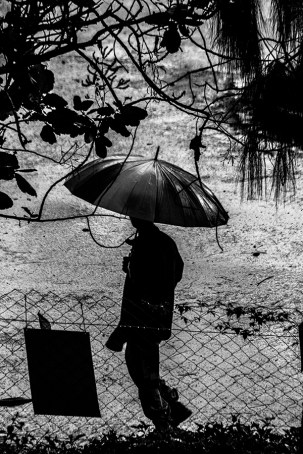 B&W shot of man walking on stree with umbrella