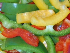 Food or catering background of sliced colorful sweet bell peppers in green, red and orange for use in a healthy fresh salad or as a flavoring in cooking