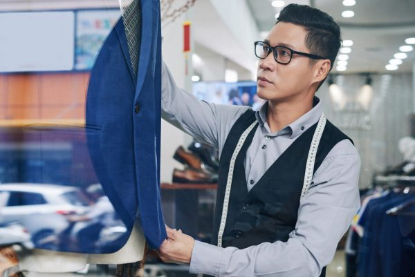 Professional Vietnamese tailor putting blue suit on mannequin
