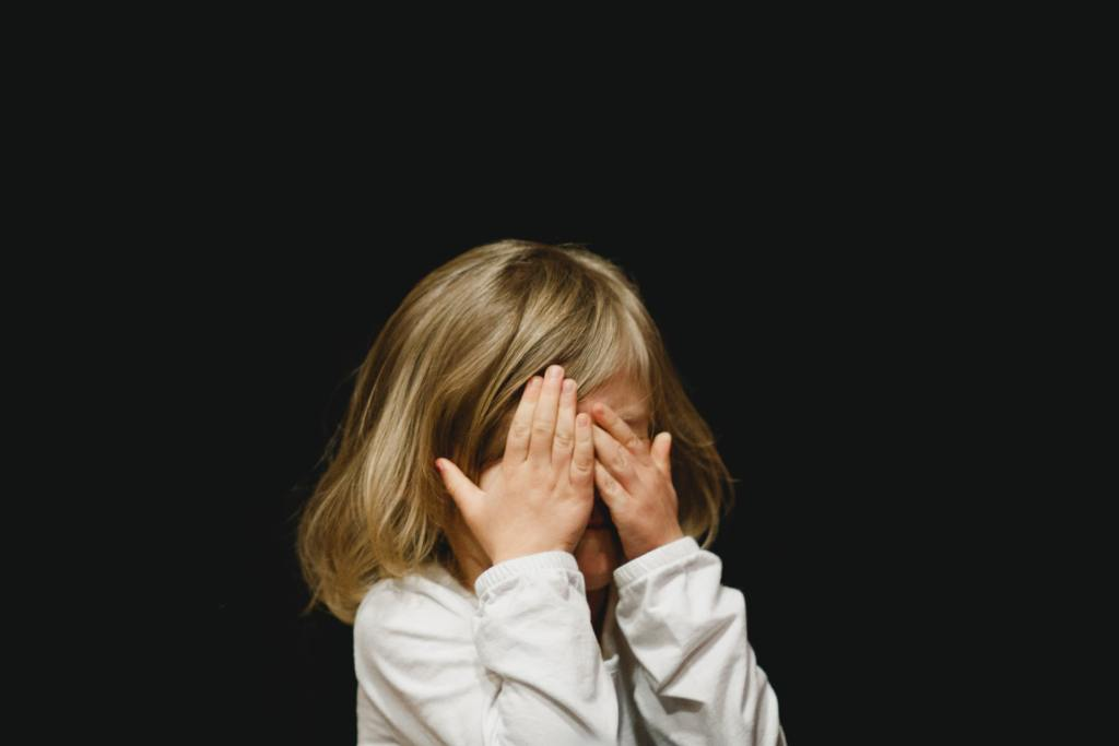 A small white child covers their face with their hands
