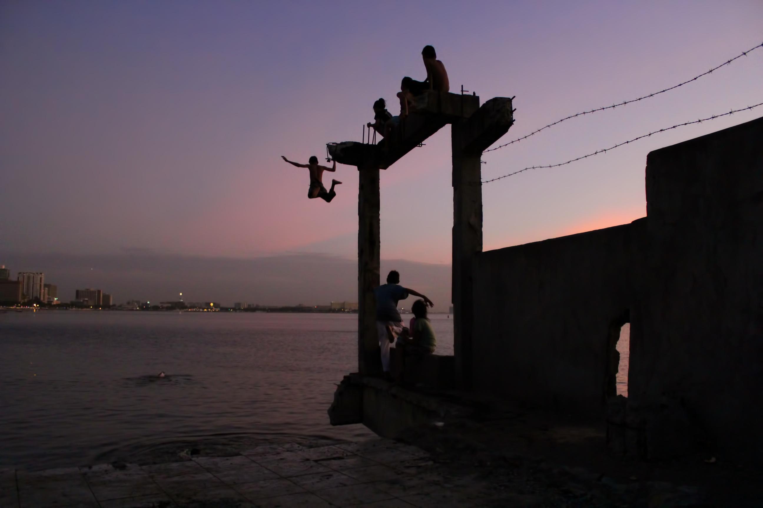 Kids playing on burnt pier in Manila