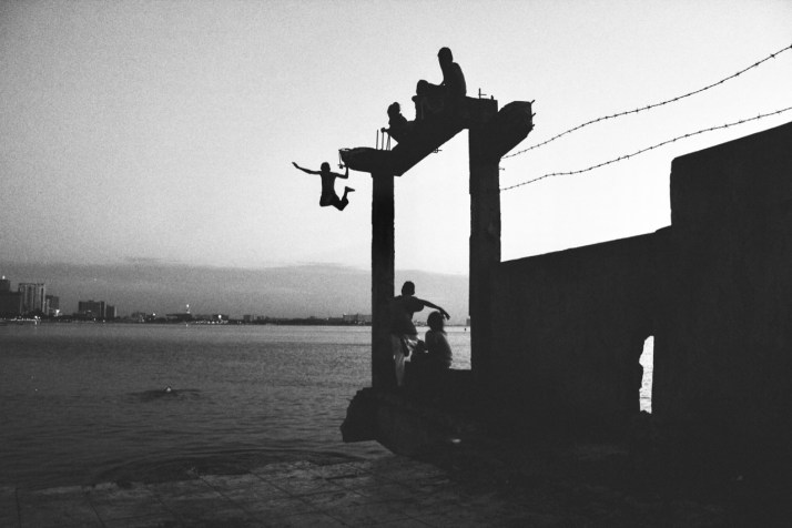 Kids leaping off a pier in Manila Bay in the Philippines