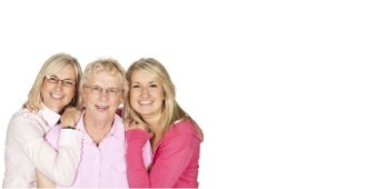Three generations of women smiling and wearing pink