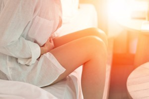 woman sitting on bed experiencing pelvic pain