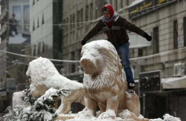 A Palestinian poses for a photograph on a snow-covered lion statue in the West Bank city of Ramallah January 10, 2013. At least 17 people have died due to a storm in Lebanon, Jordan, Turkey, Israel and the Palestinian territories. Meteorological agencies in Israel and Lebanon both called it the worst storm in 20 years. REUTERS/Mohamad Torokman
