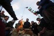 Palestinians, together with Israeli and foreign activists, gather around a fire near newly-erected tents in an area known as E1, near Jerusalem January 12, 2013. Palestinians from villages in the occupied West Bank near Jerusalem pitched tents on Friday on the land Israel has earmarked for a new urban settlement, looking to preserve the area for an independent Palestinian state. REUTER/ Baz Ratne
