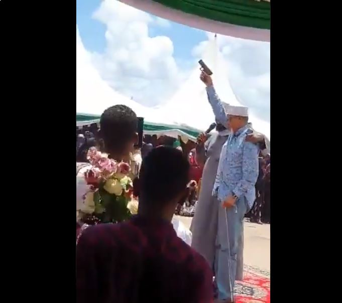 Man said to be Senator Yussuf Haji brandishing a pistol during a public function (Twitter)