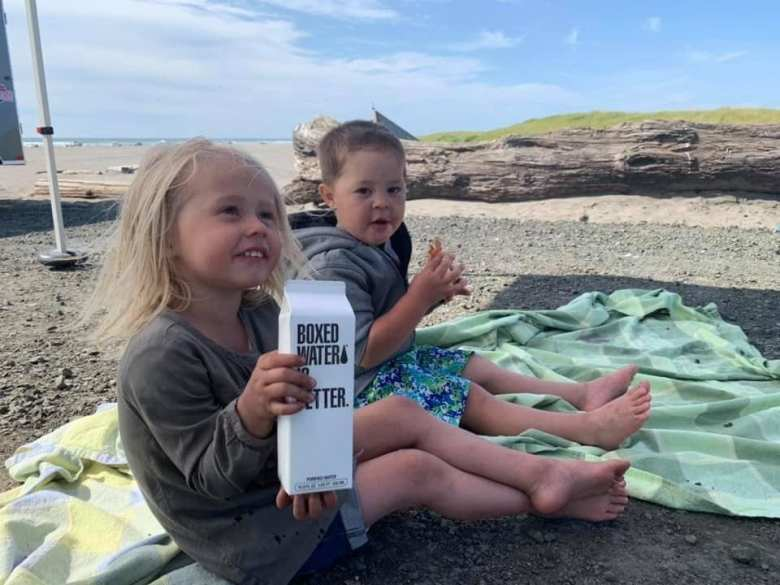 Two Children holding a boxed water after a beach cleanup