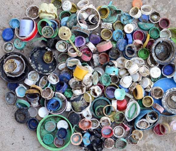 Photo of bottle caps found on a beach, less plastic more ocean.