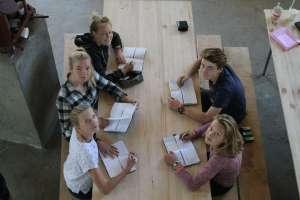 Schülerinnen sitzen an einem Tisch. Darauf liegen fünf Klarheit-Kalender