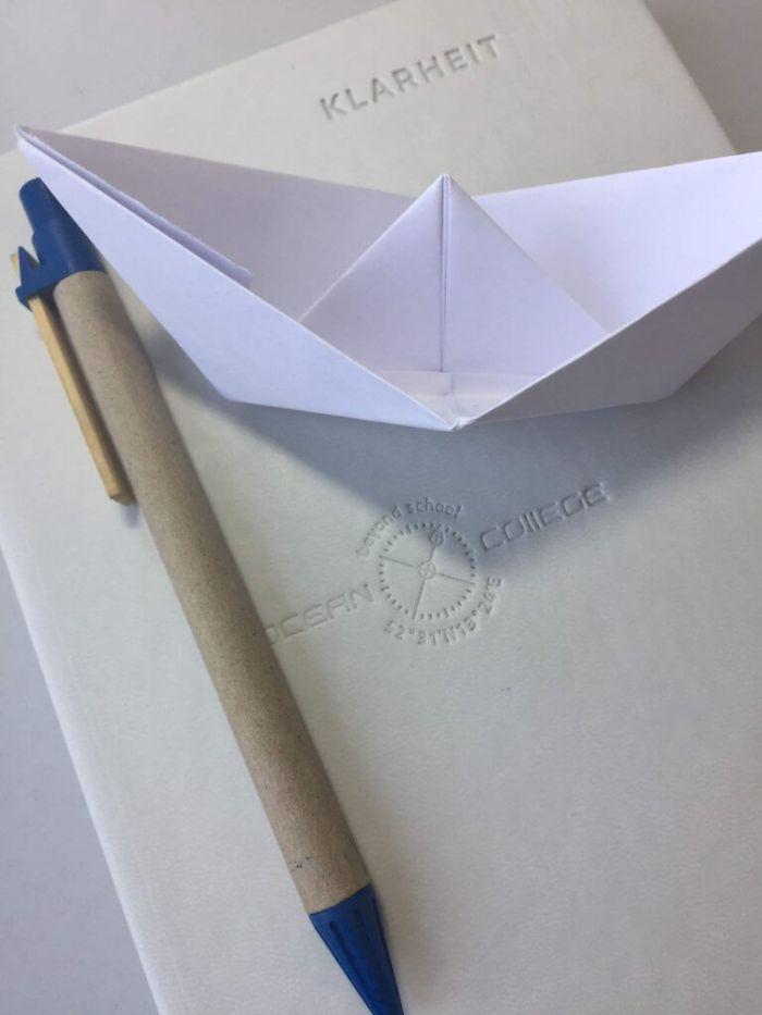 Klarheit Kalender mit einem Stift und einem Papierschiff