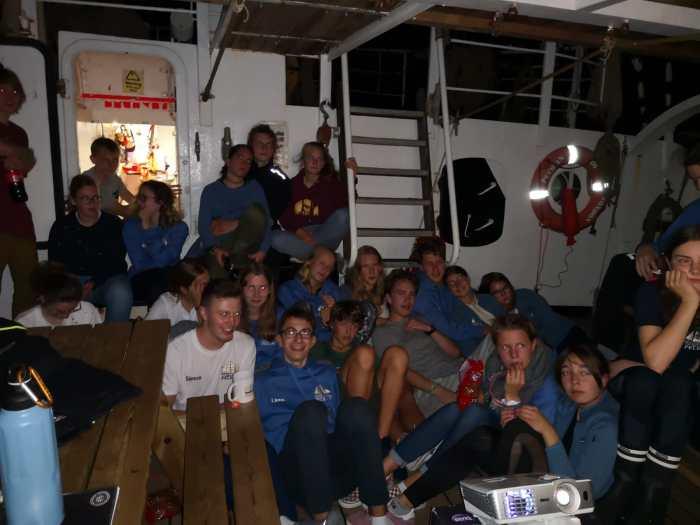 Gruppe auf dem Schiff beim Filmabend