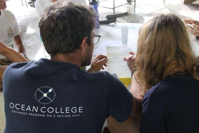 Mann im Oceancollege-T-Shirt und Mädchen sitzen an einem Tisch und reden