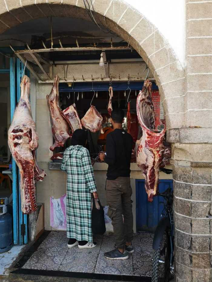 Fleischstücken hängen an Haken.