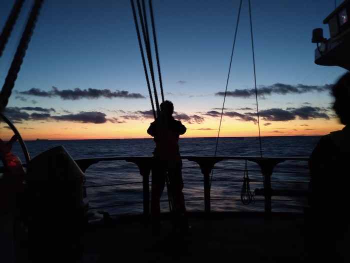 Person betrachtet den Sonnenuntergang auf dem Meer