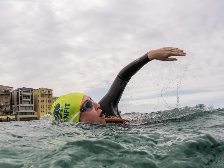 female ocean swimming with a fluro swim cap