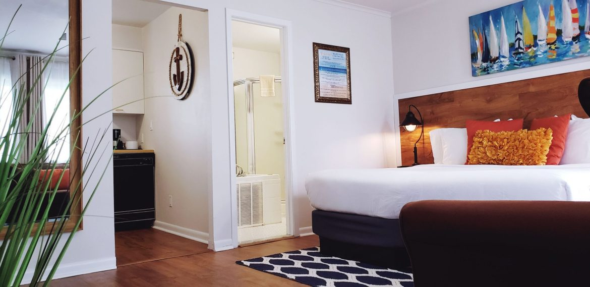 King hotel suite with colorful pillows on the bed and a doorway to the kitchen and a jacuzzi bath in the bathroom.