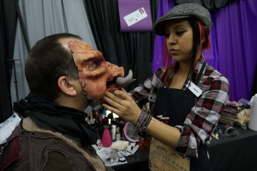 A monster having his mask applied for the haunt