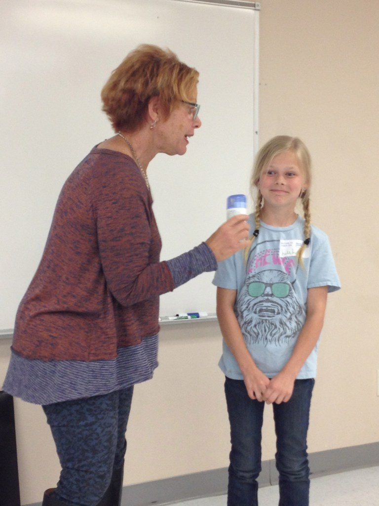 Leslie Dixon, health educator, Birds & Bees Connection, explains the process and importance of deodorant application to attendee tween Lulu Hill.