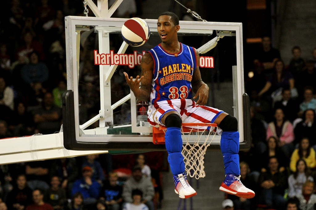 Harlem Globetrotter sitting on a basketball net