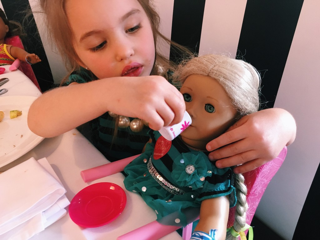 Child feeding her American Girl Doll