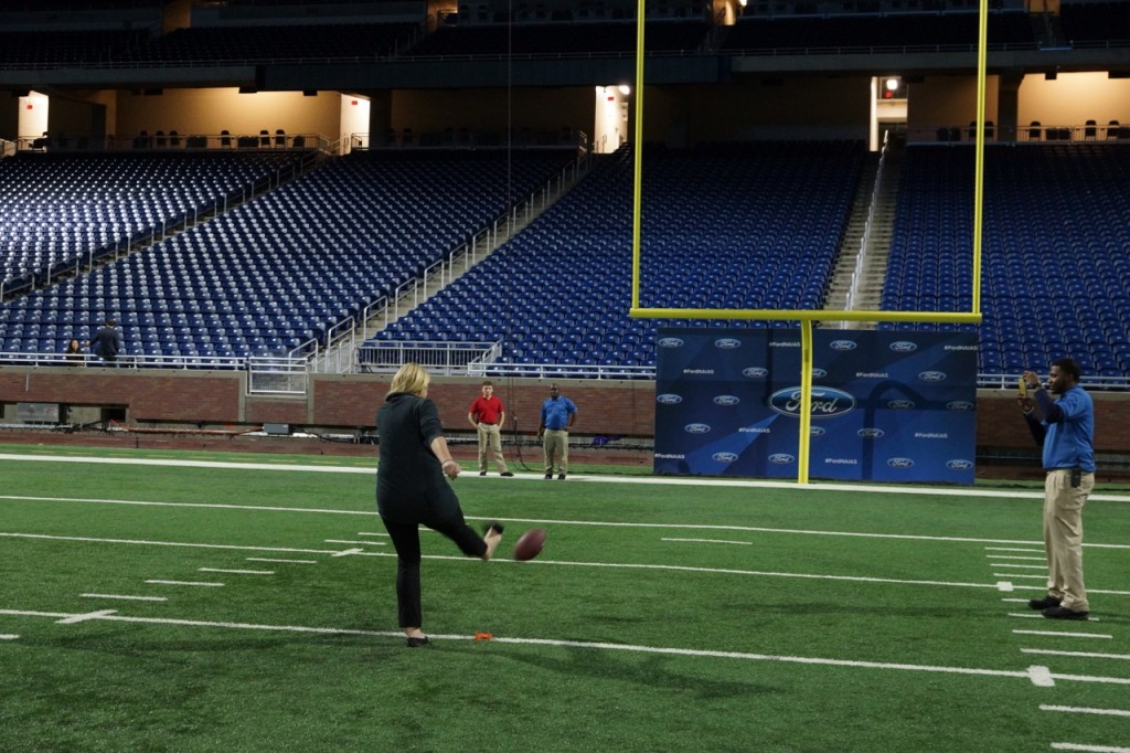 Kicking a football on the field at Ford Field