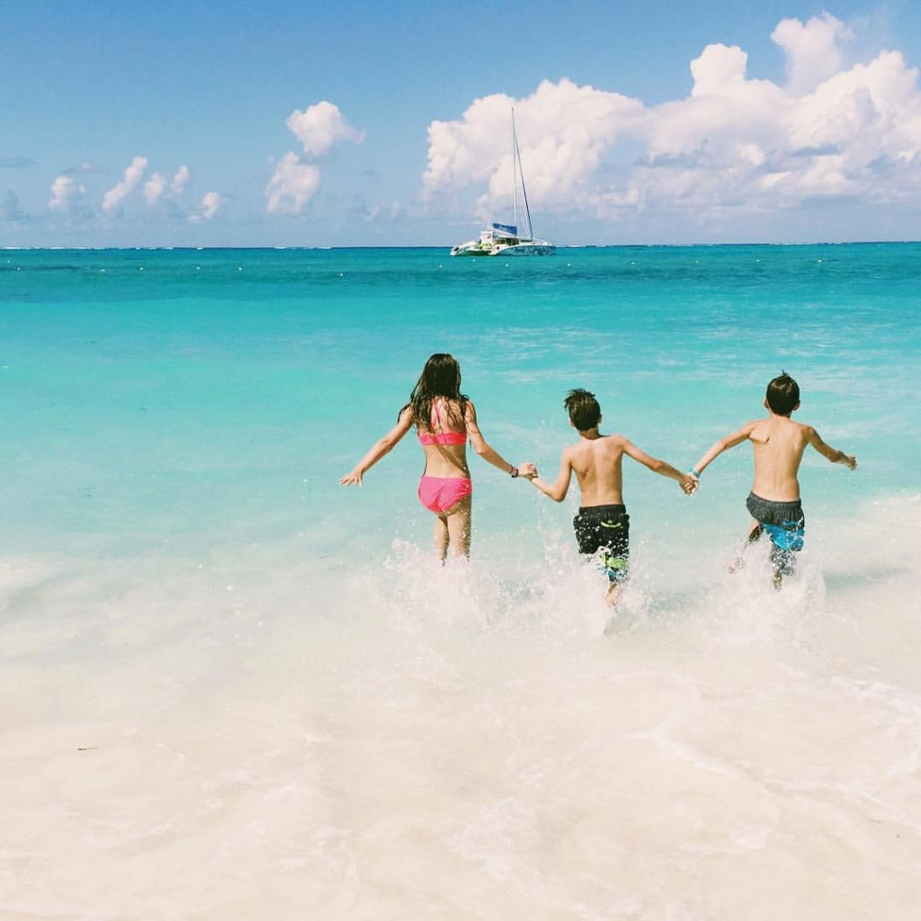 kids running into the caribbean waters