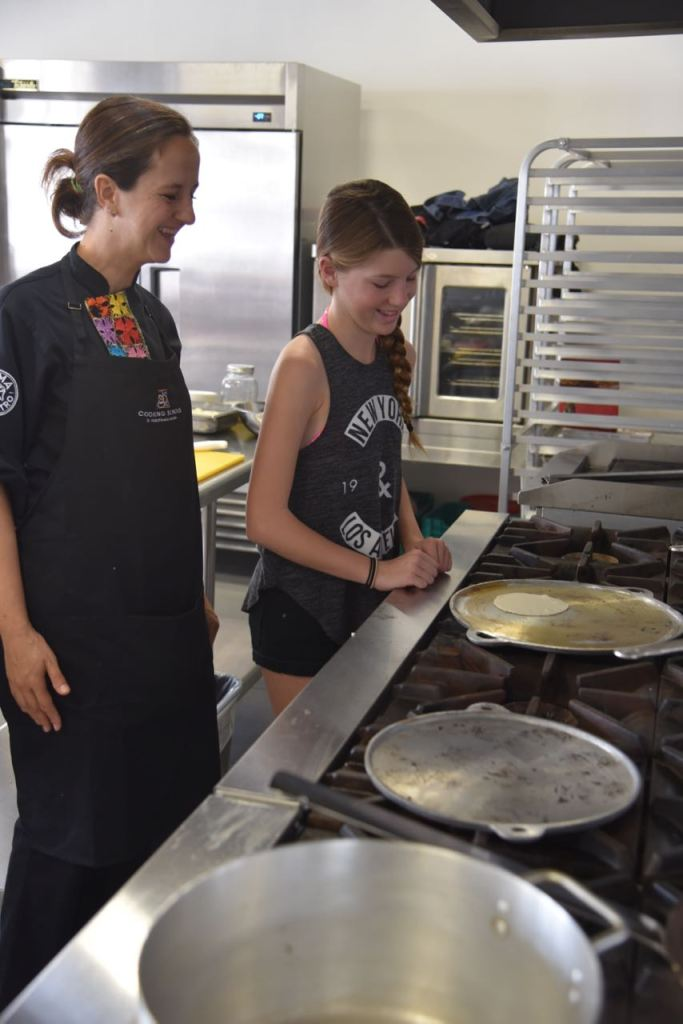 Learning how to cook a tortilla in the Mayakoba cooking school