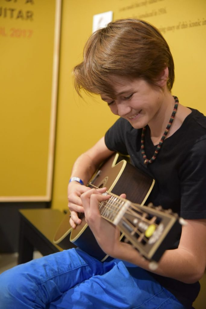 Playing a guitar at the Museum of Making Music