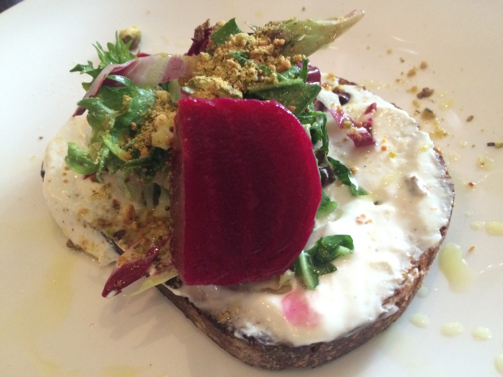 grilled bread and goat cheese spread topped with a salad of marinated beets, chicory and ground pistachios