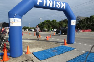 David Scott Esham crosses the 5K finish line. All of the Esham family placed in the race:  David first in the 40 to 49 men's age group; David's mom, Jen, first in the 70+ age group; wife Melinda, second in the women's 40 to 49 age group;  Dylan, first, in the 11 to 15 age group; and Damon, first in the 10 and under age group. Photo by C. Leinbach