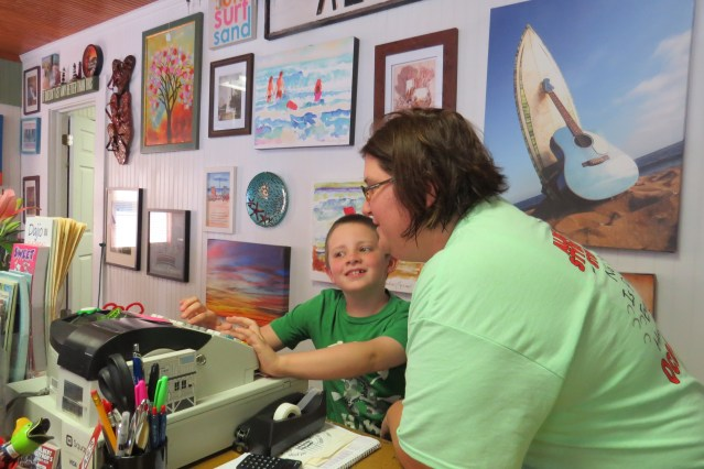 Valerie Mason teaches her son, Aidan, how to use the cash register inn the newly opened Albert Styron Store on Lighthouse Road. Photo by C. Leinbach