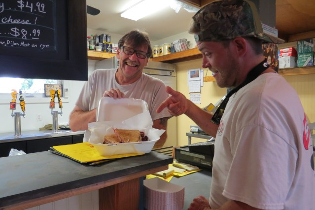 Rob Dennis, owner of the School Road Deli in Spencer's Market serves an artisan sandwich to islander James Stewart, right. Photo by C. Leinbach