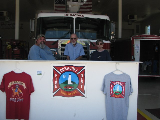 T-shirt sales provide income for the Ocracoke Volunteer Fire Department. Helping out are longtime volunteers Albert O'Neal, fire chief, Dick Jacoby, president of the OFPA, and Janey Jacoby, treasurer of the OFPA. Photo by P. Vankevich