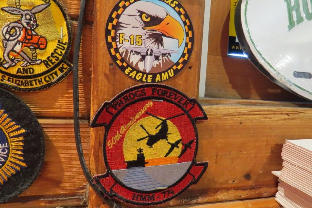 Part of the military patch collection on Howard's Pub walls, the patch at bottom right show the Marine Corps Phrogs unit.