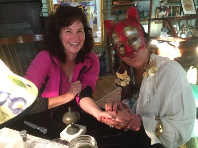"""Melinda Sutton gets her palm read by """"Zelda"""" at an Ocracats fundraiser Oct. 22 at Roxy's antiques."""