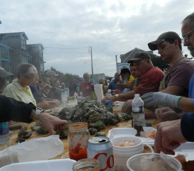 Oyster Roast attendees dig into a freshly steamed pile of the bivalves.