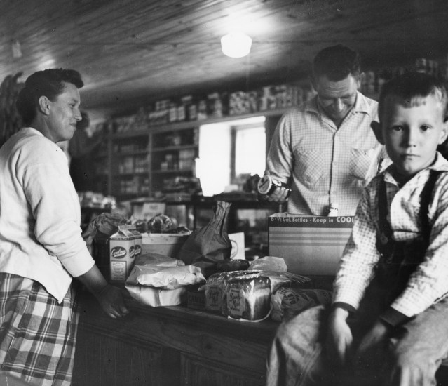 """Iona Teeter, and her son Carl """"Toad"""" Teeter purchase sundries from Monkford Garrish at The Community Store, 1955. Photo from the Standard Oil Collection by Martha McMillan Roberts, courtesy of Ekstrom Library."""