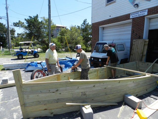 It's not a real boat Ocracoke students are crafting outside their shop studio on Back Road. It will be a replacement shell boat for the Pirate's Chest. Working on it are, from right, Hunter O'Neal and Grant Jackson under the watchful eye of teacher Jeff Schleicher. Photo: C. Leinbach