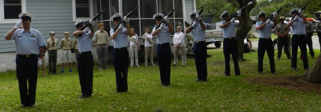 The Coast Guard Honor Guard gives the 21-gun salute.