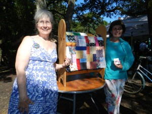 """Elizabeth Smith of Greenville, right, won the raffle of the """"block party"""" quilt. Islander Debbie Leonard, left, helped make the quilt with the Ocracoke Needle and Thread Club. Photo: C. Leinbach"""
