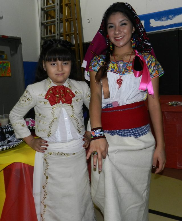 La estudiante de primer año de la escuela Ocracoke Stephanie Flores Esparsa, a la izquierda, y la novena alumna Vanessa Lora modelan la ropa tradicional de México. Lora más tarde fue coronada reina del festival por vender las entradas más 50-50.grader Vanessa Lora model traditional clothing from Mexico. Lora later was crowned queen of the festival for selling the most 50-50 tickets.