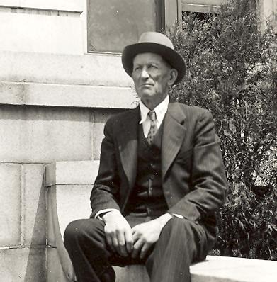 John G. Ellenbecker sitting outdoors on a bench