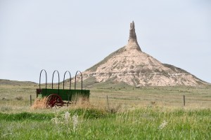 covered wagon sits in grasslands in front of large sandstone formation