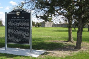 large sign with text near tree in front of historic fort