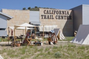 exterior of building with covered wagon and campsite in front