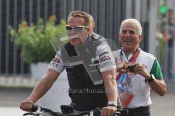 © Octane Photographic Ltd. 2011. Formula 1 World Championship – Italy – Monza – 11th September 2011. Race Day in the Paddock. Michael Schumacher riding his bike into the paddock. Digital Ref : 0193LW7D6405