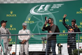 World © Octane Photographic Ltd. Gerard Butler drinks from the race boot of Red Bull Racing's Daniel Ricciardo whilst Mercedes' Lewis Hamilton and Nico Rosberg watch. Sunday 23rd October 2016, F1 USA Grand Prix Podium, Austin, Texas – Circuit of the Americas (COTA). Digital Ref :1750LB1D4716