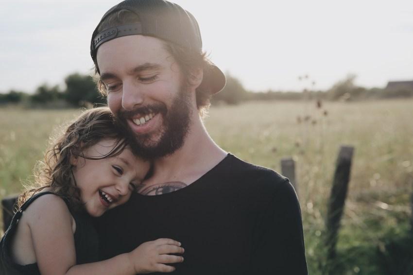 ojciec z dzieckiem na ręku, uśmiechnięty